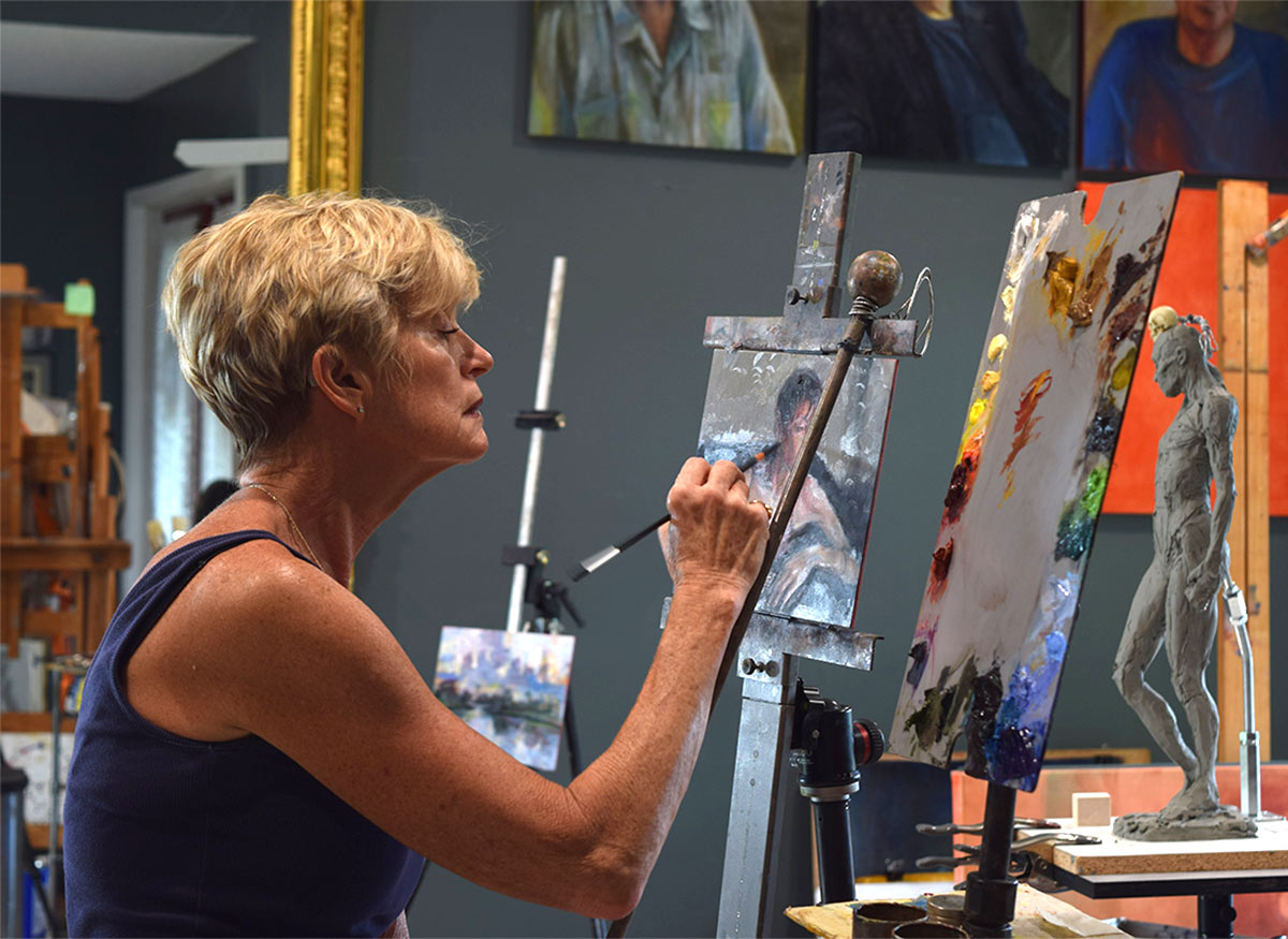 Picture of Artist Elizabeth Reed Painting in her studio